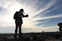 Young woman photographs the panorama at sunset. Plovdiv, Bulgaria.