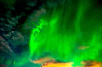Aurora Borealis behind colorful clouds in Iceland.