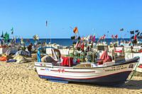 Fishing floats and flags set out to dry in the sun at Monte Gordo beach, Algarve, Portugal.