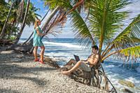 Man working on the beach. Attractive man with laptop seated in a palm tree on a tropical beach. Young man working on laptop computer on the tropical b...