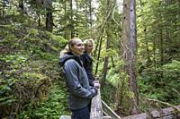 North America, Canada, British Columbia, Vancouver Island, Pacific Rim National Park Reserve, . two female tourists hiking on the rainforest trail.