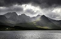 White house under Blaven mountains of Black Cuillin Hills with sun rays under dark clouds at Loch Slapin Isle of Skye Scotland UK.