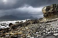 Tourists on rocks of Elgol beach at Port na Cullaidh with Red Cuillin Mountains under clouds on Loch Scavaig Isle of Skye Scotland UK.