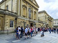 People queueing to visit the Roman Baths, Bath, Somerset, England, UK. The Roman Baths is a well preserved and historical site from Roman times built ...