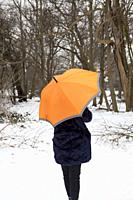Woman with Umbrella in Snowy Park in London UK