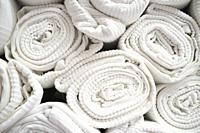 Loads of rolled white cotton bedspreads. Closeup.