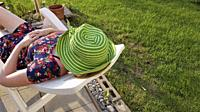 A woman with a bright green hat naps on a plastic chair, Consecon, Canada.