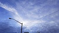 Late afternoon coudy sky, airplane contrail, and streetlights, Windsor, Canada.