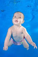 Little baby learns to swims underwater in pool on a blue water background. Healthy family lifestyle and children water sports activity.