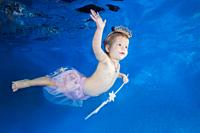 Little girl with a magic wand swimming underwater. Healthy family lifestyle and children water sports activity. Child development, disease prevention.