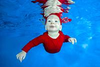 Funny face portrait of little baby boy in red costume swimming and diving underwater with fun in pool on a blue water background. Healthy family lifes...
