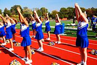 A youth cheerleading squad leads the spectators to root for the home team.