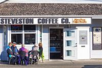 Customers enjoying autumn sunshine and coffee in Steveston Village British Columbia.