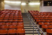 Row of empty chairs, with stairs in the middle, in an auditorium.