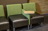 Two identical chairs, with a desk between them, in a college lobby.