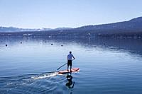 Young man seen from behind as he standup paddles at Lake Tahoe.