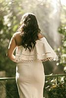 Rear view of a woman in white dress standing outdoors.