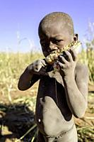 Portrait of a naked Himba boy eating a corncob.