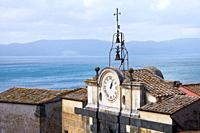 view of Lake Bracciano with ancient clock and bells, Anguillara Sabazia, Lazio, Italy.