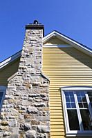 Natural stone chimney on the exterior wall of a yellow cladded with white trim contemporary country style residential home in spring, Quebec, Canada.