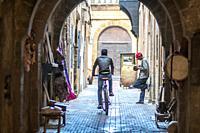 Man Riding a Bicycle Down an Alley, Essaouira, Marrakesh-Safi, Morocco.
