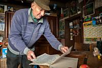 Friendly elderly man in his kitchen showing his hand-written book with notes about the weather and important incidents. Germany.