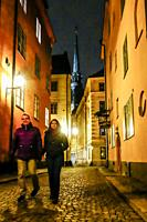 Stockholm, Sweden A couple walking on Old Town or Gamla Stan with the German Church in the background.