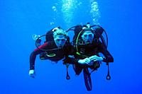 Diving couple swiming in the deep sea, Indian Ocean, Maledives, South Asia.