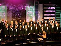 Woman conducting a traditional welsh male voice choir singning in competition for best choir in Wales.