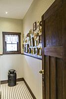 Guest bathroom with old milk collecting pail and assorted picture frames on the wall inside a LEED certified Country home
