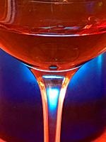 Glass of red wine against blue background, Close view.