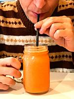 Man sipping fruit juice with a straw.