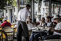 Waiter serving customers at traditional outdoor Parisian cafe in center city.