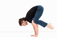 Casual dressed young adult man making yoga exercises on white background.