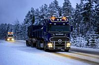 Salo, Finland - January 25, 2019: Two trucks, Scania V8 for limestone haul in the front at speed with beautiful lights lighting up the dark rural road...