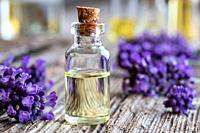 A bottle of essential oil with fresh lavender flowers on a rustic wooden background.