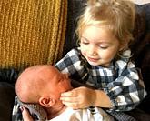 Little blond girl, 3 years old, loving her baby sister in Ystad, Scania, Sweden.