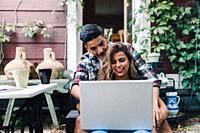 Smiling young couple sitting embraced in the steps of their wooden house with a laptop.