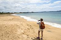 Woman takes a photo on the beach in Pataua, Northland, New Zealand.
