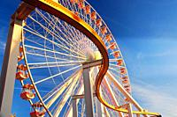 A curving rail cuts in front of a large Ferris wheel.