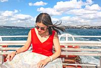 Beautiful Chinese woman looks at Istanbul map while cruising in Istanbul,Turkey.