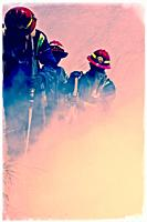Firemen tackle a brush fire in the heat of the day. Cape Town, South africa.