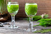 Two glasses of barley grass juice with freshly grown blades.