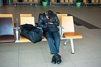 Singapore, Republic of Singapore, Asia - A passenger is sleeping next to his hand luggage in a public area at Terminal 1 of Singapore's Changi Airport...