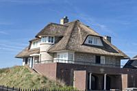 Netherlands, zeeburg, 2017, An stunning example of a thatched roof on a red bricked house looking out over the north sea. While once a sign of poverty...