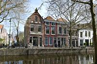 Netherlands, Gouda, 2017, cyclist passing in front of traditional houses on the banks of a canel.