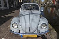 Netherlands, Gouda, 2017, An old volkswagen beetle, parked along the side of a canal or grachten. In the background the typical architecture of the ci...