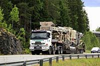 Sisu semi trailer of Telamurska Oy transports Metso Lokotrack crusher on scenic road. The machinery weighs 100000 kg. Salo, Finland - June 30, 2018.