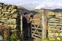 Two walkers at a gate in the Coppermines Valley in the Lake District National Park near Coniston, Cumbria, England.