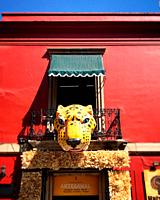 A head of a jaguar decorates a red building in Oaxaca, Mexico